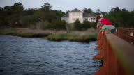Young boys lean over dock railing, pull empty crab-trap out of river and toss it back in