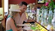 Young Brazilian couple fix plates at restaurant salad bar