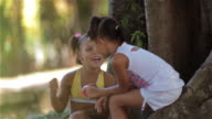 Young Brazilian girls gossip and play with ball on string in public park