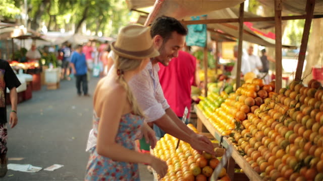 Young Brazilian man juggles oranges to impress girlfriend at open-air farmers market in Rio