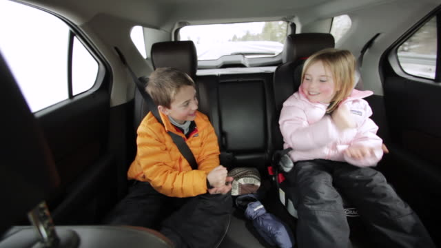 MS POV Young brother and sister playing 'shoot' in  back seat on road trip / Sun Valley, Idaho, United States