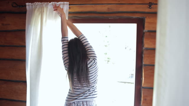 Young brown woman waking up from bed, pulling the curtain and stretching her arms.