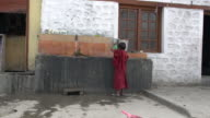 Young Buddhist monk about 7 years old doing dishes outside the school kitchen at Samstanling Monastery, Nubra Valley, Ladakh, India