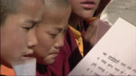 CU Young Buddhist monks reading religious texts outdoors / Lo Manthang, Mustang, Nepal