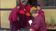Young Buddhist monks remove their shoes before entering a classroom. Available in HD.