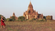 MS Young Buddhist monks walk past a temple in procession carrying alms bowls / Bagan, Myanmar