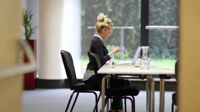 Young business executive syncing smartphone with laptop