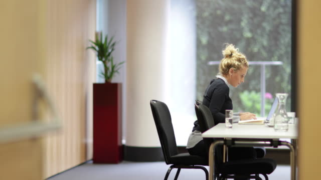 Young business executive working on laptop in a meeting room