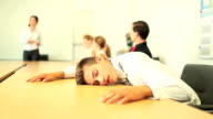 Young business man asleep on the boardroom table