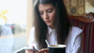 Young business woman browsing her smartphone in the coffee shop.