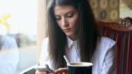 Junge Geschäftsfrau Durchblättern Ihrem smartphone im coffee shop.