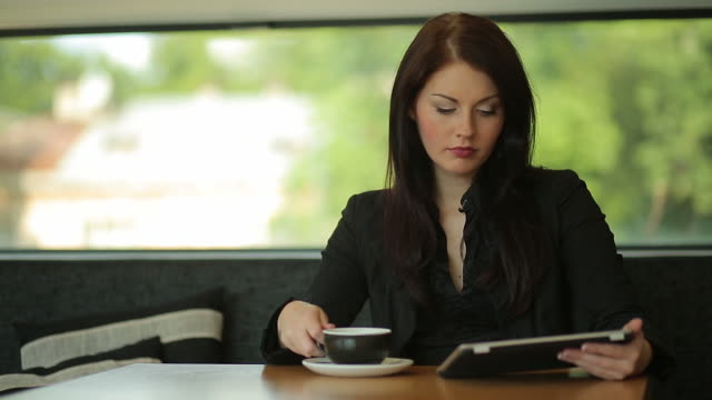 Young Business Woman is Using Digital Tablet in Cafe