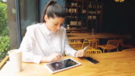 Young business woman making online payments using digital tablet.