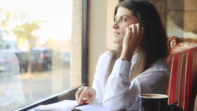 Young business woman talking on the phone and writing notes.