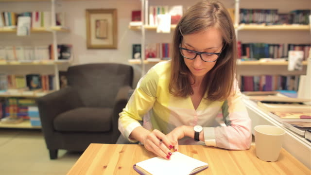 Young business woman writing notes in a bookstore.