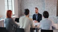 Jonge zakenman communiceren met leden van de menselijke hulpbronnen, terwijl ze op een sollicitatiegesprek.