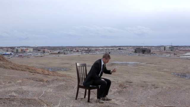 MS Young businessman dressed in black suit trying to get reception for his cell phone while sitting on  chair on top of  bluff in rural area / Maple Grove, Minnesota, United States