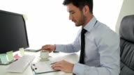 Young businessman drinking coffee while working at the office