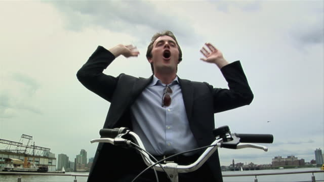 MS, LA, Young businessman on bicycle talking on Bluetooth headset and cheering, New York City, New York, USA