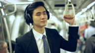 MS Young Businessman on subway train wearing headphones