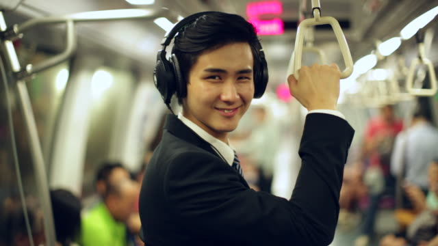 MS Young Businessman on subway with headphones smiling