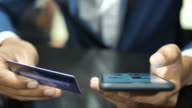 Young businessman paying bills and using online banking on mobile phone