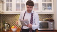 Young businessman reading a newspaper in the kitchen