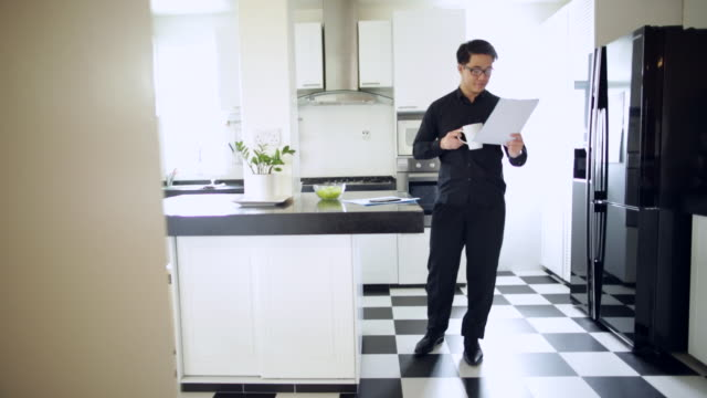 WS Young businessman reading report in kitchen
