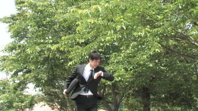Young businessman running, looking at watch