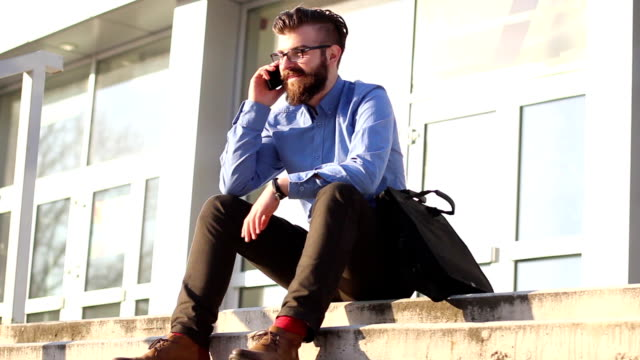 Young businessman sitting on stairs and talking on the phone