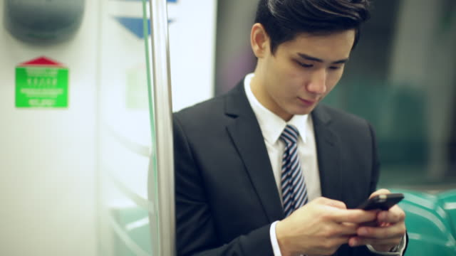 MS Young Businessman sitting on subway train using smartphone