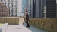 Young Businessman Skateboarding Between Office Buildings