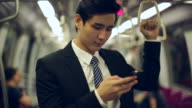 MS Young Businessman standing on subway train using smartphone