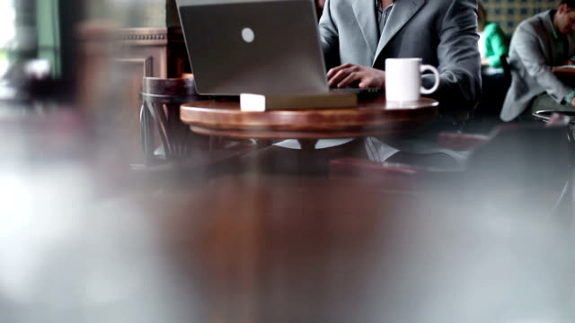 Young businessman typing at laptop and drinking coffee.