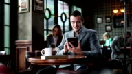 Young businessman using digital tablet at the cafe.