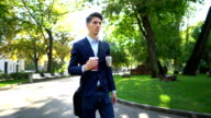 Young businessman walking and holding coffee and newspaper
