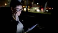 Junge Geschäftsfrau mit einem Digitaltablett im Auto.