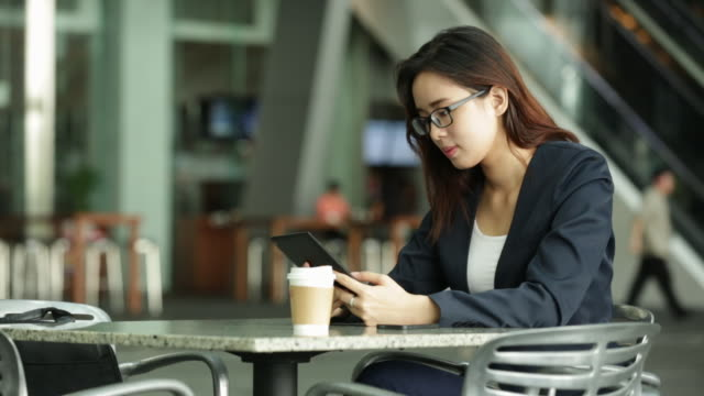 Young businesswoman using digital tablet and phone at cafe