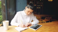 Young businesswoman working in a coffee shop, writing notes and using digital tablet.