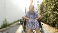 Young caregiver take care elderly woman on wheelchair