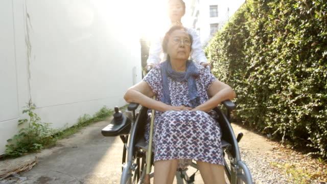 Junge fürsorgliche um ältere Frau im Rollstuhl