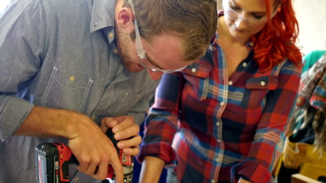Young Caucasian man drilling hole in wood with power drill in community woodworking workshop