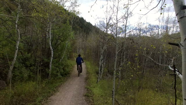 A young Caucasian man rides his bicycle on a mountain trail