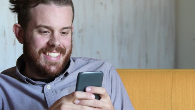 Young Caucasian man with beard using smartphone
