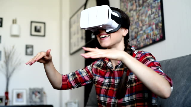 Young Caucasian woman playing  using white virtual reality headset glasses