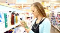 Junge kaukasischen Frau Geschäfte für Duschgel in persönliche Pflege der Supermarkt Gang