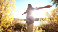 Young cheerful woman arms outstretched in nature