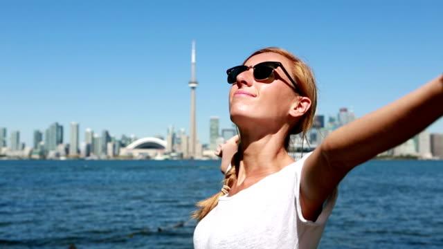 Vrolijke jongedame in Toronto-Canada uitgestrekte armen