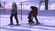 A young child shuffles through the snow on skis.