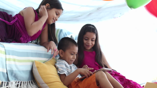 Young children at home using digital tablet.